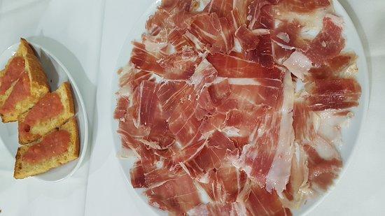 Jamón ibérico cortado en el momento con tomate, aceite y pan crujiente