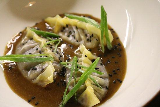 La Traviesa: Dumpling de rabo de al vapor sobre un fondo y curry