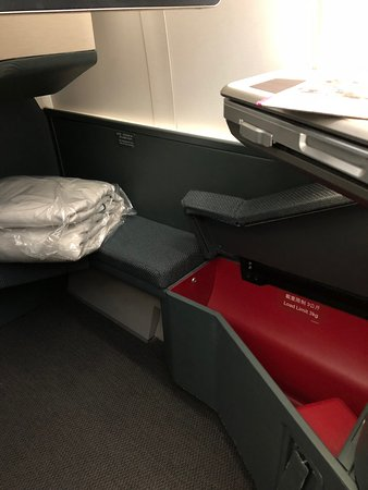 Cathay Pacific: Triangular side storage locker under window