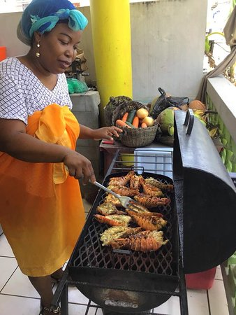 Authentic Flavors: Lobsters being grilled on BBQ by one of the chefs Marcia Augustine pic by Jamaul Roots