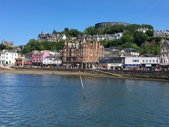 Oban, UK: McCaigs Tower and town frontage from sea level.