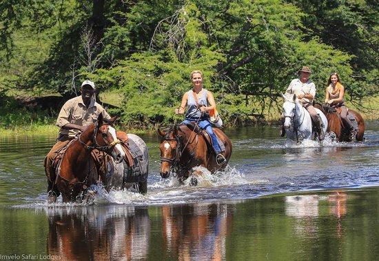 Hwange, Zimbabwe: Horse riding crossing a pan on the Ngamo Plains.
