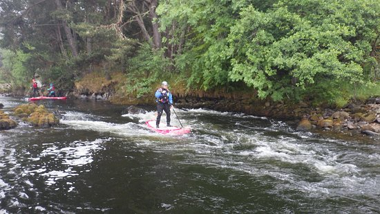 Rothes, UK: SUP boarding a wee rapid on the river Spey.