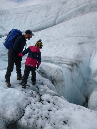 Kennicott, AK: Our guide Nick is showing my son a moulin.