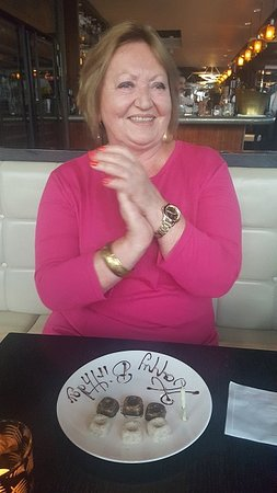 Londres, UK: Restaurant surprised mum with chocolates and birthday candle.
