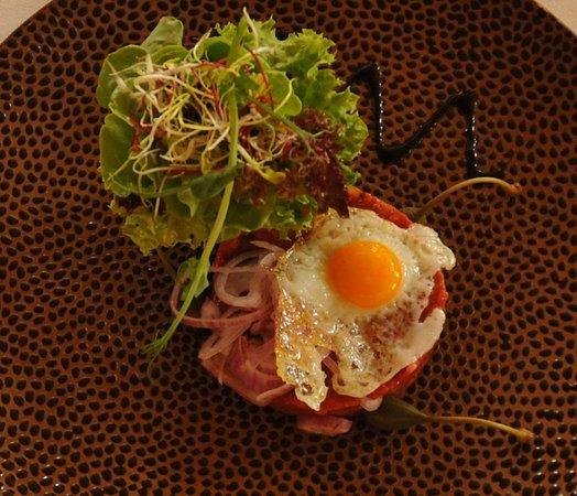 Bonaduz, Switzerland: Steak Tartare with a quail egg, dressed green salad and red onion