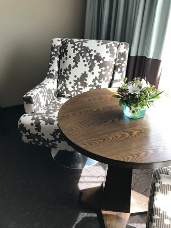 Seating area in room, 2 swivel chairs w/table and fresh wild flowers