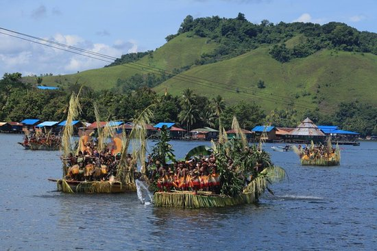 Sentani, Индонезия: People from 9 tribes rowing the boat