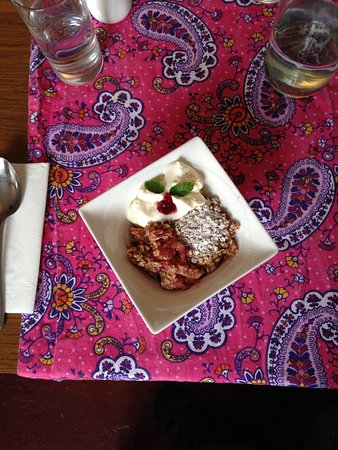 Annascaul, Irlandia: apple raspberry crumble with whipped cream and mint leaves