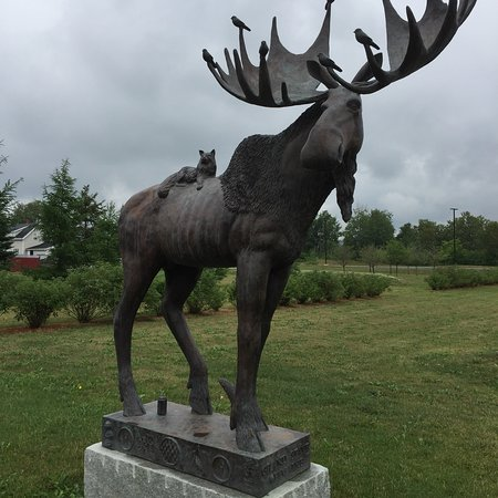 Van Buren, ME : A life-size bronze moose statue has be accessorized with a Maine Coon Cat, lobsters, a can of Mo