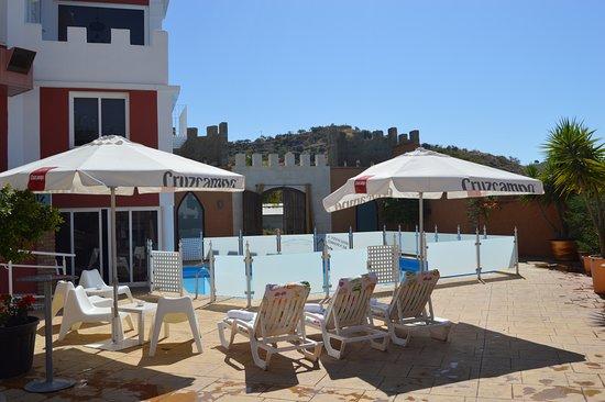 Arenas, Spain: Zona de la piscina de día con las hamacas y las sombrillas