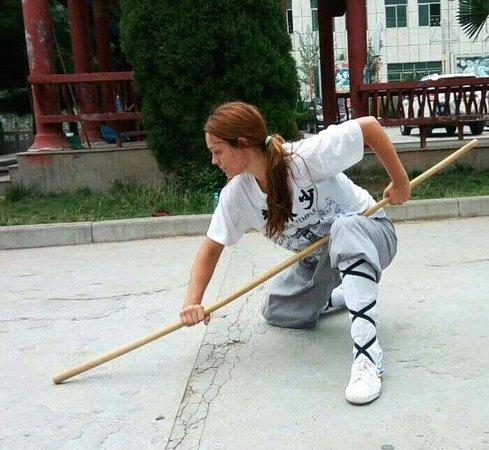 Tancheng County, China: student playing Kung fu stick