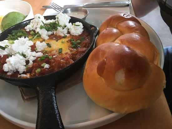 Shakshooka eggs with feta topping and a side challah roll.