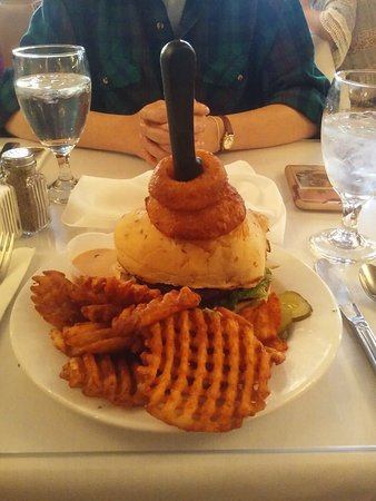 My meal of fries and BQQ Burger with onion rings on top. (Knife is sticking up to help cut burge