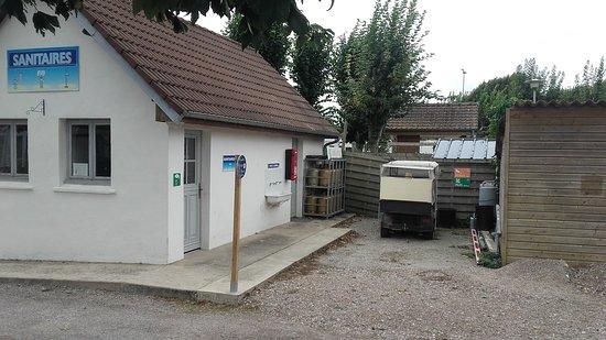 Camping Le Walric: Vue de l'emplacement S1 sur un ancien bloc sanitaire maintenant local maintenance et espace fume