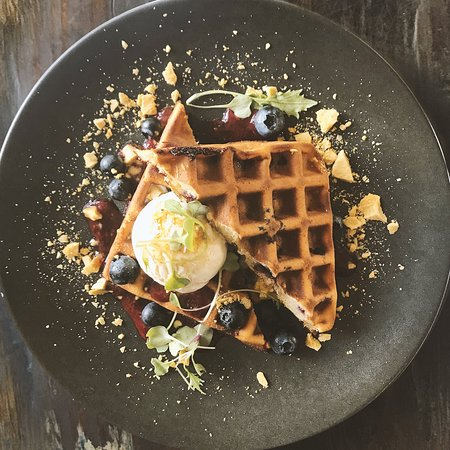 Blueberry buttermilk waffle with honey comb, vanilla bean ice cream & berry coulis