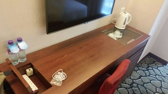 GDH Hotel: work desk with charging station on one side and refreshment drawer on the other.