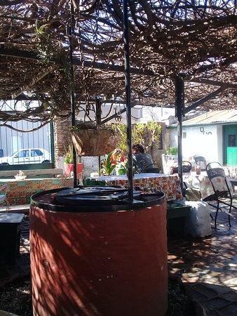 Epoca de Quesos: Patio, con aljibe. las mesas están debajo de una glorieta, donde se aprecia la decoración del pa