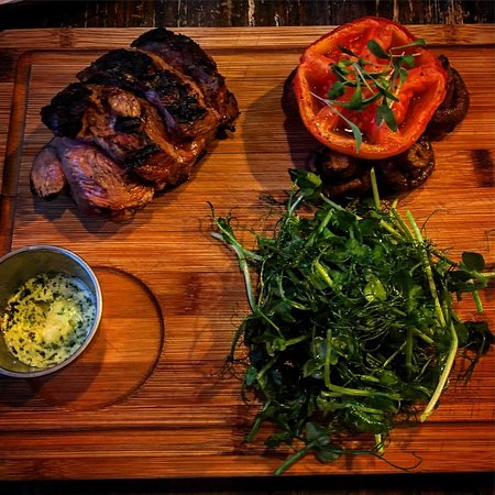 Grilled lamb rump with a confit tomato, mushrooms, a green salad and some melted garlic butter.