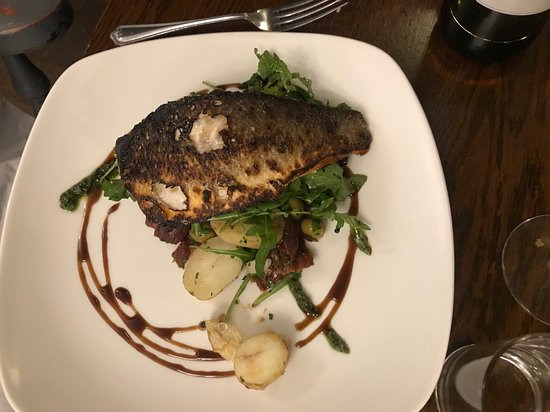 Finchampstead, UK: Sea-Bass on a bed of potatoes and squid, with sun-dried tomatoes and olives