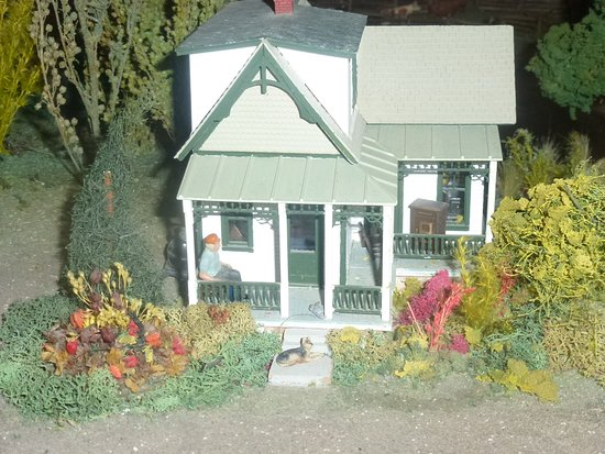 House By Tracks With Man Relaxing On Porch And Dog On The