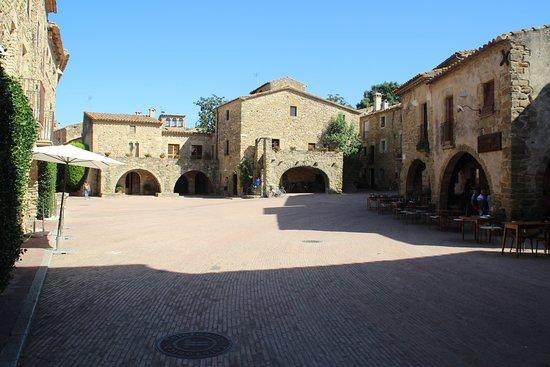 Monells, Spain: Vista de la Plaza. L'Arcadi esta en el lado izquierdo al sol de mediodia.