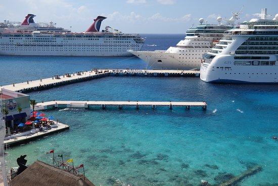 View of cruise ship port to left of hotel. Colored umbrellas are the corner  of Bubba Gumps - Picture of El Cid La Ceiba Beach Hotel, Cozumel -  Tripadvisor