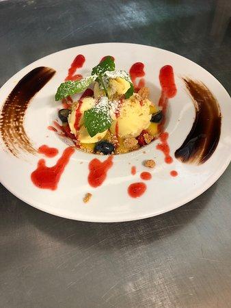 Gelato alla vaniglia su una mousse di mango e coulis di fragola e amaretto croccante