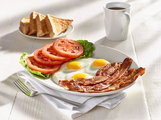 Five strips of premium bacon, three eggs, and freshly sliced tomatoes served with thick toast.