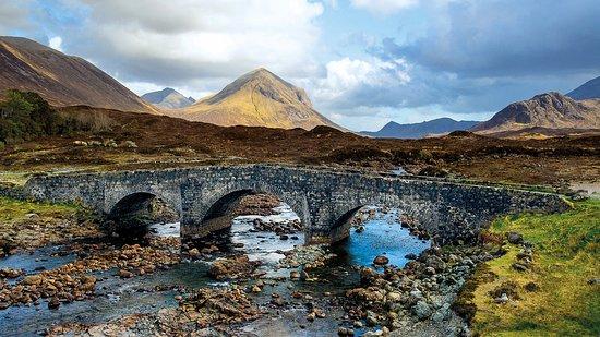 Die alte Brücke bei Sligachan mit den Cuillin Hills dahinter. Sligachan ist ein hervorragender Ausgangspunkt für Wanderungen in die Bergwelt der Isle of Skye im Westen Schottlands.