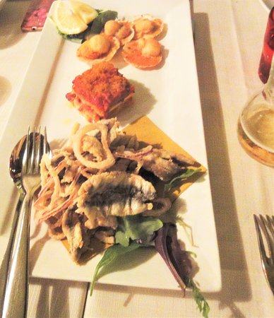 Antipasto caldo costituito da alici fritte, parmigiana di spigola e canestrelle gratinate.