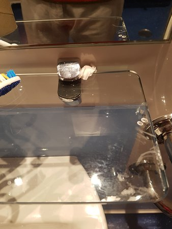 Shelf above sink held in place on both sdies by toilet paper to stop it slipping out of it's holders