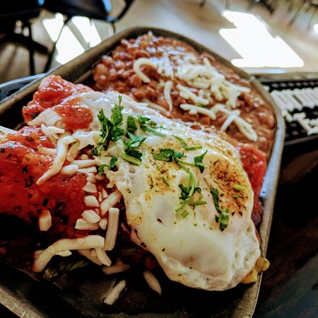 Enchiladas Rancheras. Breakfast Enchiladas made of chorizo and bacon and topped with a fried egg.