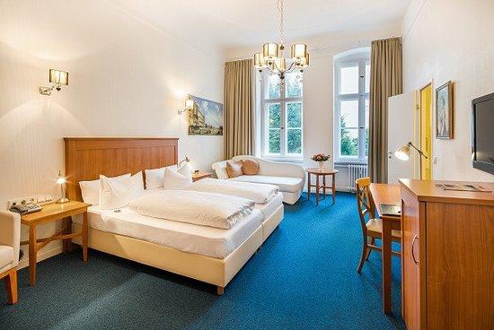 Zimmer 12 Deluxe Kategorie mit Doppelbett, Sitzgruppe, modernen Standardbad und Gartenblick.