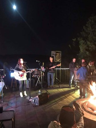 Laona, WI: Nashville recording artist Rylie Bourne, entertaining on Johnnie's veranda with family and friends, with the full moon over Waubicon Lake.