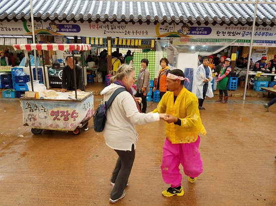 Gimje, Sør-Korea: The gentleman selling candy did a little dance with his shears,  and Gina decided to dance with him.
