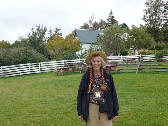 Take the Island Adventure Day Tours : In front of Anne of Green Gables House wearing hat with braids supplied by Bill.