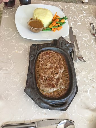 Sizzling steak with potatoes, vegetables and sauce