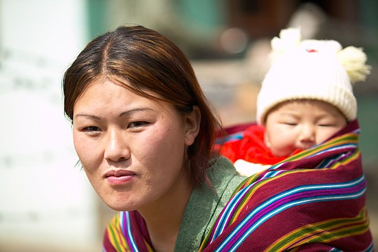 Bhutanese women still prefer to carry their baby at their back with a piece of woven fabric popularly called as Kabney.