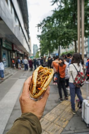 Чэнду, Китай: A long line of people wait to get their hands on this delicious pita-like sandwich!