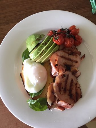 "Our ""Avocado Grove Special"" breakfast, poached egg on toast with spinach, avocado, tomatoes and bacon."