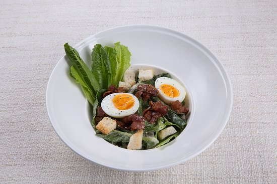 Caesar salad with boiled egg, bacon and croutons in Chef's homemade Caesar dressing