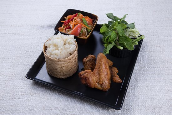 A set of fried chicken wings served with sticky rice and Thai-style papaya salad