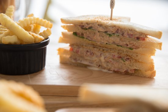 Grilled tuna and cheese sandwich with lettuce and tomato served with fries
