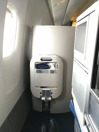 British Airways: Business class window seat with foot rest up. Access to aisle it just to the right of the footrest, at the end of the partition on the right.