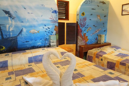 """Inside of beachfront bungalow """"Chinchorro"""". With private roof terrace and view over the ocean. The bed setting (a queen size bed and one individual bed) is perfect for a couple with one child."""