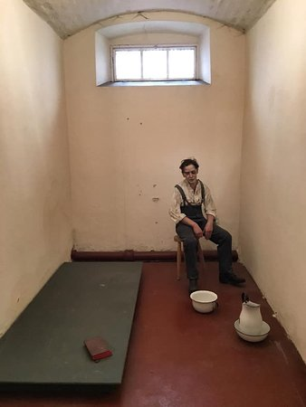 Recreation of a harsh cell used for punishment of prisoners — just slab bed with no mattress, a chamber pot, ewer and basin, and a Bible.