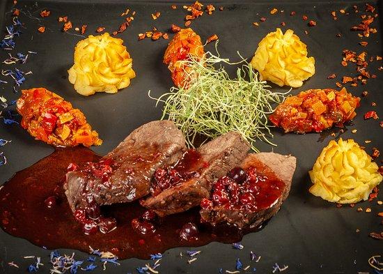 Томленный окорок лося с соусом из лесных ягод, дополненный взбитым запеченным картофелем и кабачковой икрой.