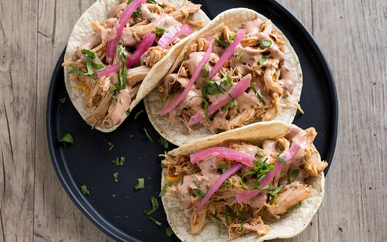 Sharky's Chipotle-Braised Chicken Tinga Tacos - Slow cooked chicken thighs, Sharky's sauce, pickled red onions, cheese, cilantro; non-GMO corn tortilla