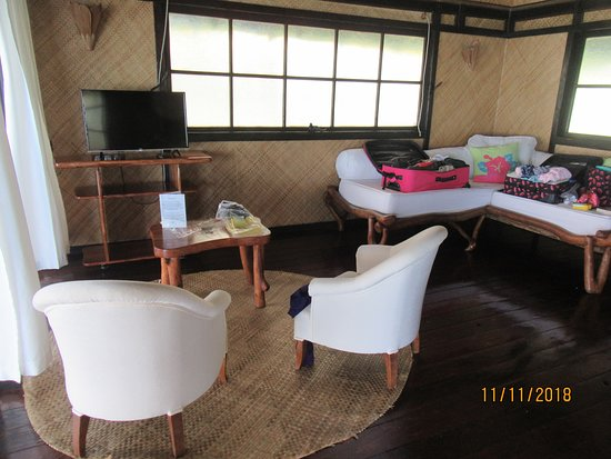 sitting area in beach suite; large windows can be propped open; curtains to the left are the glass doors facing water